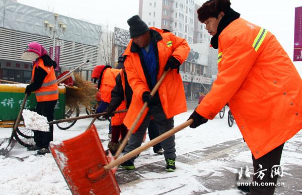 环卫工人扫雪作业-天津迎来首场降雪 津南百名环卫工人全力清雪图片